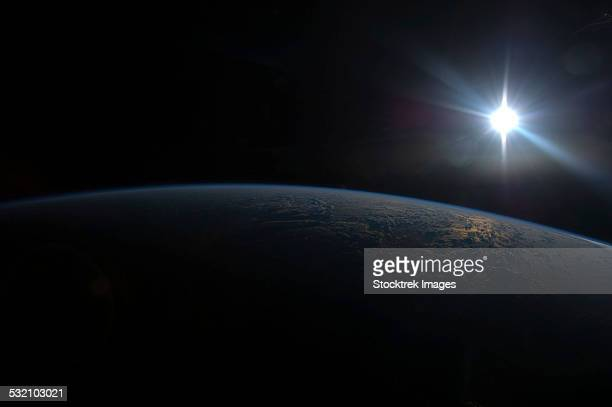 June 2, 2013 - View from space of the Sun setting over Earths horizon.