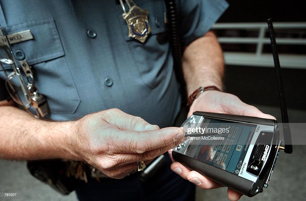 Massachusetts State Trooper Barry Newell does a passenger check with a handheld computer at Logan International Airport June 20, 2002 in Boston, Massachusetts. The wireless device allows officers to perform background checks for criminal histories, arrest warrants and immigration status. The computers are one of the security changes made since the September 11, 2001 terrorist attacks, where two of the four September 11 flights departed from Logan.