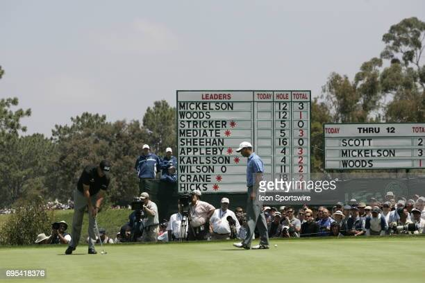 Phil Mickelson taps in for birdie on the 13th hole as Tiger Woods watches on during the first round of the US Open Championship at Torrey Pines South...