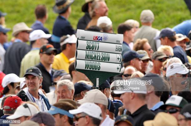 The scoreboard with Scott Mickelson and Woods on it makes its way through the crowd during the first round of the US Open Championship at Torrey...