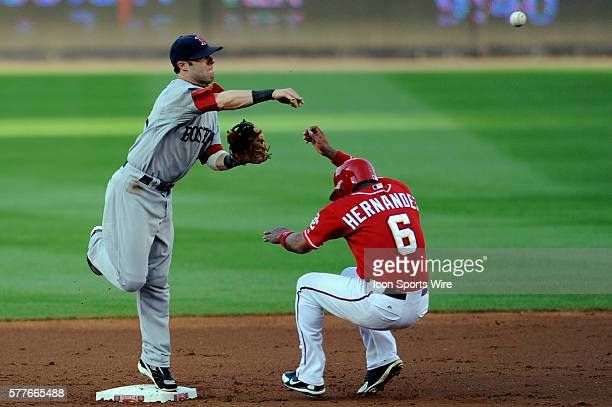 Boston Red Sox second baseman Dustin Pedroia turns a double play on a ball hit by Washington Nationals catcher Wil Nieves to force out second baseman...