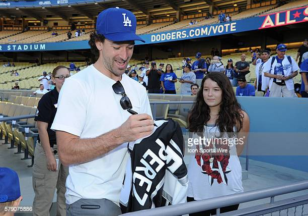 Los Angeles Kings player and Conn Smythe trophy recipient Justin Williams signs autographs for eager Dodger and Kings fans prior to a Major League...