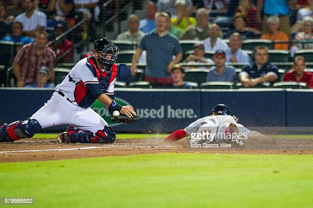 Boston Red Sox Second Baseman Brock Holt beats the throw to home during a regular season game between the Boston Red Sox and the Atlanta Braves at...