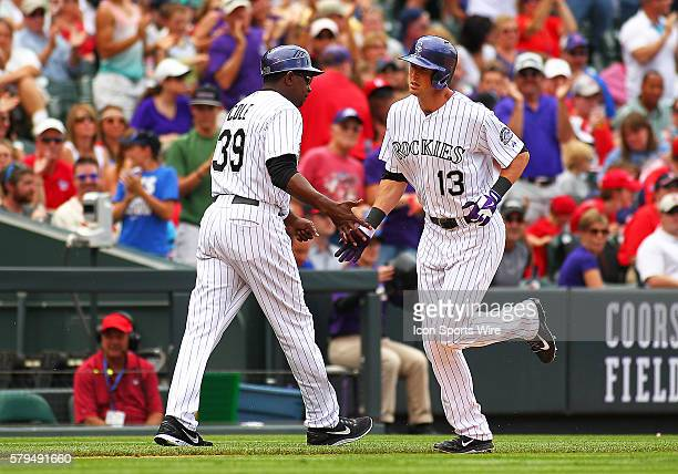 Colorado Rockies Third Base Coach Stu Cole congratulates Outfielder Drew Stubbs as he rounds the bases after connecting for a homerun during a...