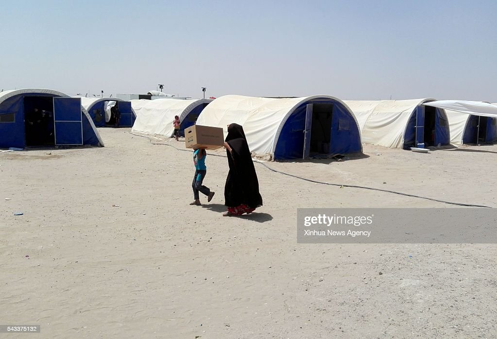 FALLUJAH, June 27, 2016 -- A boy carries relief goods in a camp for internally displaced people who fled from battles between the Iraqi army and the Islamic State in Khalidiya, Iraq, on June 27, 2016.