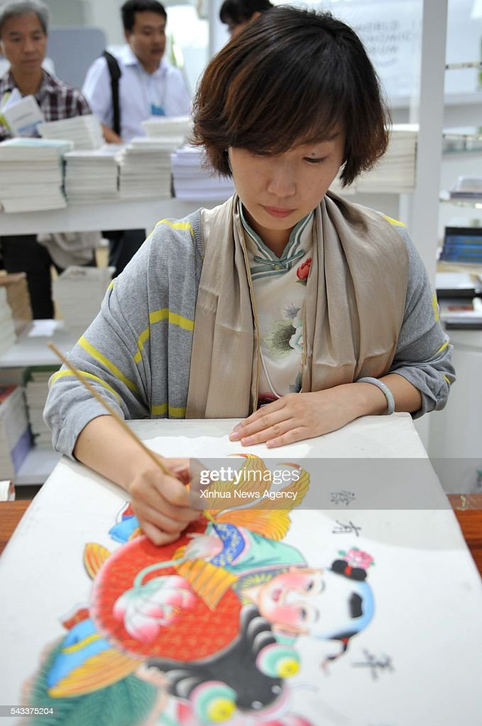 TIANJIN, June 27, 2016 -- A woman makes Yangliuqing wood engraving pictures at Tianjin display area during the Summer Davos Forum in Tianjin, north China, June 27, 2016.