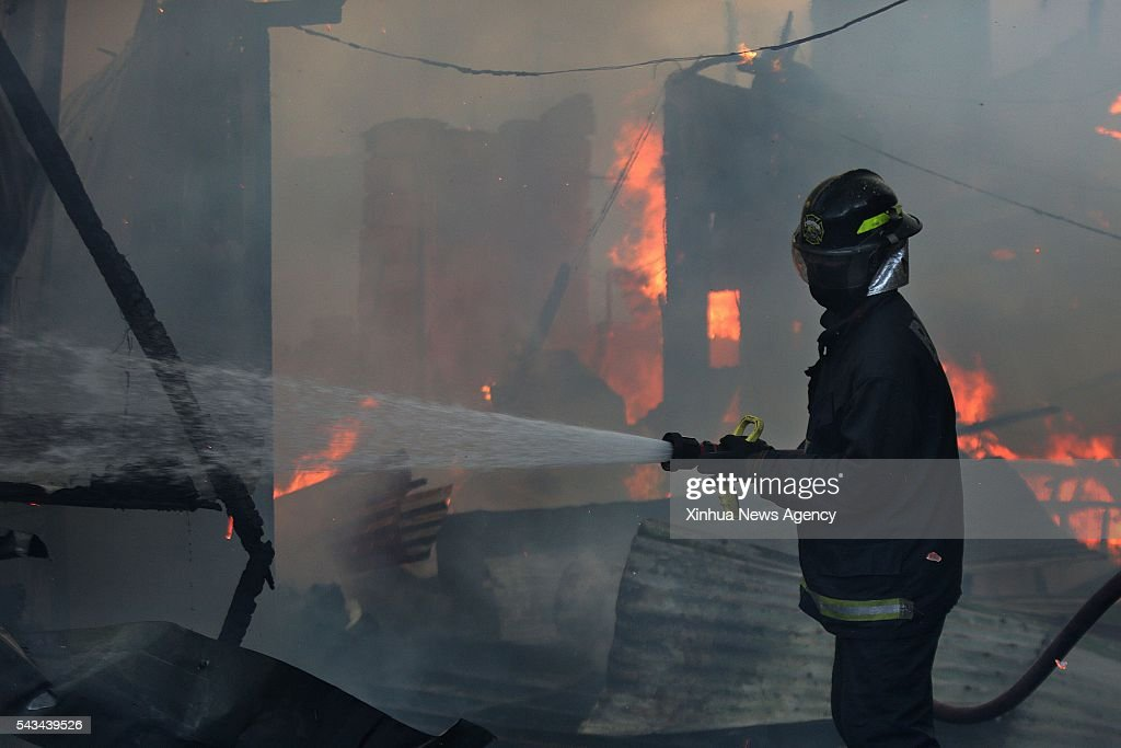 CITY, June 28, 2016 -- A firefighter tries to put out a fire at a slum area in Quezon City, the Philippines, June 28, 2016. More than 300 shanties were razed in the fire, leaving 600 families homeless, according to the Philippine Bureau of Fire.