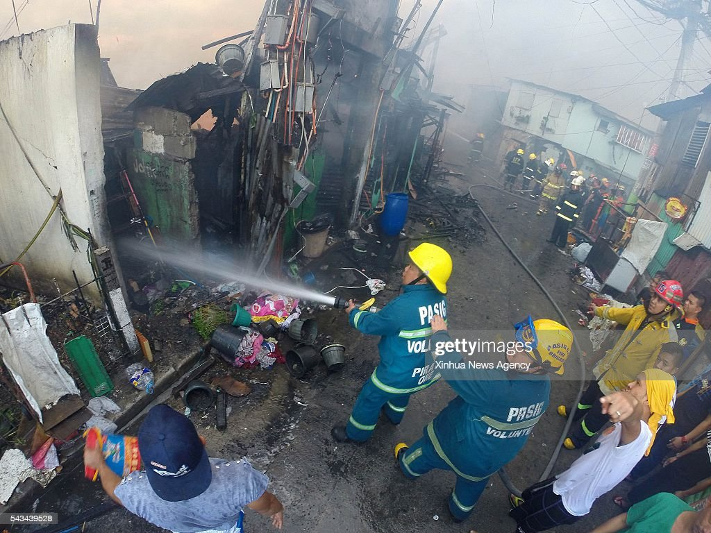 CITY, June 28, 2016-- Firefighters try to put out a fire at a slum area in Quezon City, the Philippines, June 28, 2016. More than 300 shanties were razed in the fire, leaving 600 families homeless, according to the Philippine Bureau of Fire.
