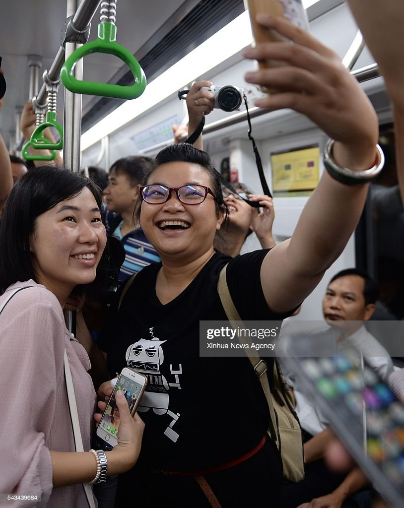 NANNING, June 28, 2016 -- Passengers take selfie on a train of subway line 1 in Nanning, capital of south China's Guangxi Zhuang Autonomous Region, June 28, 2016. The east section of subway line 1, the city's first subway line, started trial operation on Tuesday.