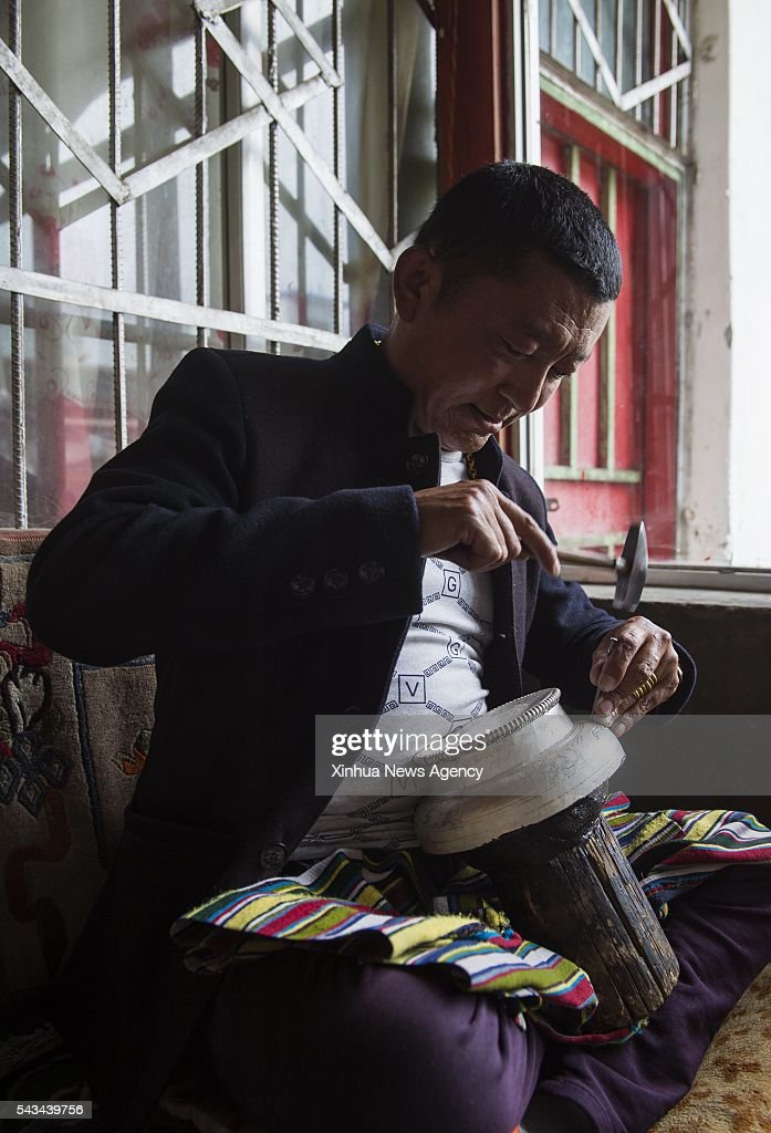 LHASA, June 28, 2016-- Photo taken on June 18, 2016 shows a craftsman working in 'Zhaxi Jicai' gold, silver and bronze ware factory in Xigaze, southwest China's Tibet Autonomous Region. The Zhaxi Jicai is a historic gold, silver and bronze ware factory in Xigaze, which was once a workshop specialized in processing and making hardwares used in Tibetan Buddhism monasteries.