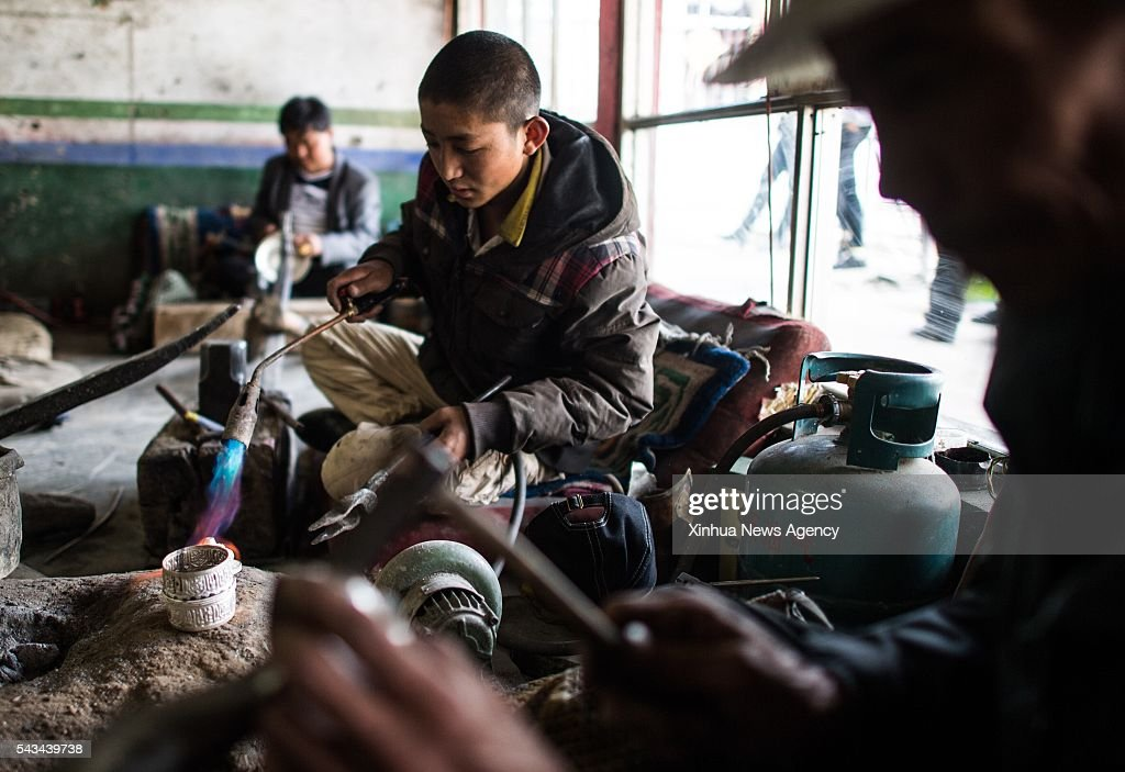 LHASA, June 28, 2016 -- Photo taken on June 18, 2016 shows craftsmen working in 'Zhaxi Jicai' gold, silver and bronze ware factory in Xigaze, southwest China's Tibet Autonomous Region. The Zhaxi Jicai is a historic gold, silver and bronze ware factory in Xigaze, which was once a workshop specialized in processing and making hardwares used in Tibetan Buddhism monasteries.