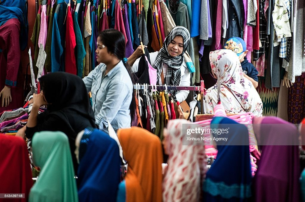 JAKARTA, June 28, 2016 -- Women select clothes at Tanah Abang market in Jakarta, Indonesia, June 28, 2016. People from and around Jakarta flood into Tanah Abang market to buy new clothes for the upcoming Eid al-Fitr festival which marks the end of the fasting month of Ramadan.