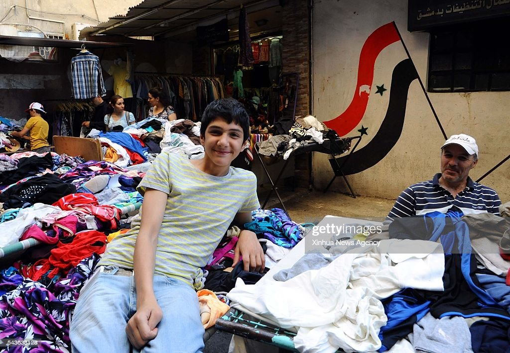 DAMASCUS, June 29, 2016 -- A Syrian vendor leans on a stall of second-hand clothes in Damascus, capital of Syria, on June 28, 2016. More Syrians in Damascus choose to buy second-hand clothes recently as they can't afford the increasing price of new clothes. Especially the Muslims buy new attires as a tradition in preparation for the upcomming Eid al-Fitr Feast.