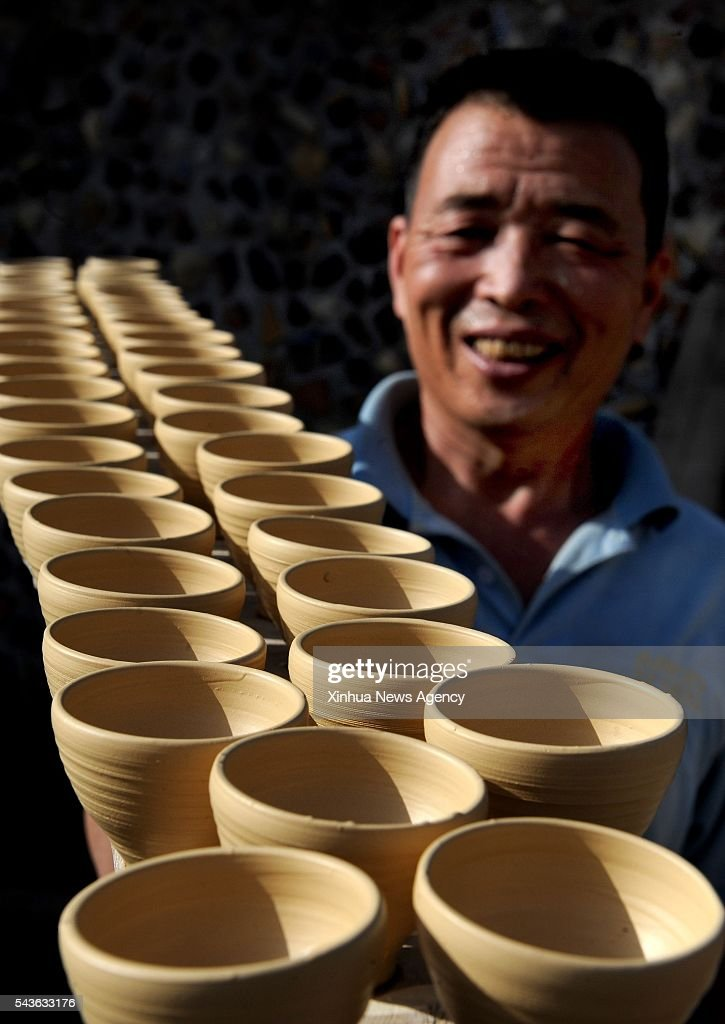 CHENGCHENG, June 29, 2016-- Folk artist Liu Zhongyang carries semifinished bowls of blue and white porcelain in the Yaotou Kiln tourist zone in the Yaotou Township of Chengcheng County, northwest China's Shaanxi Province, June 26, 2016. The site of old folk kilns, covering an area of four square kilometers, has a history of making ceramic products for over a thousand years. The techniques of making ceramics in Yaotou Kiln was listed in the National Intangible Cultural Heritage in 2006.