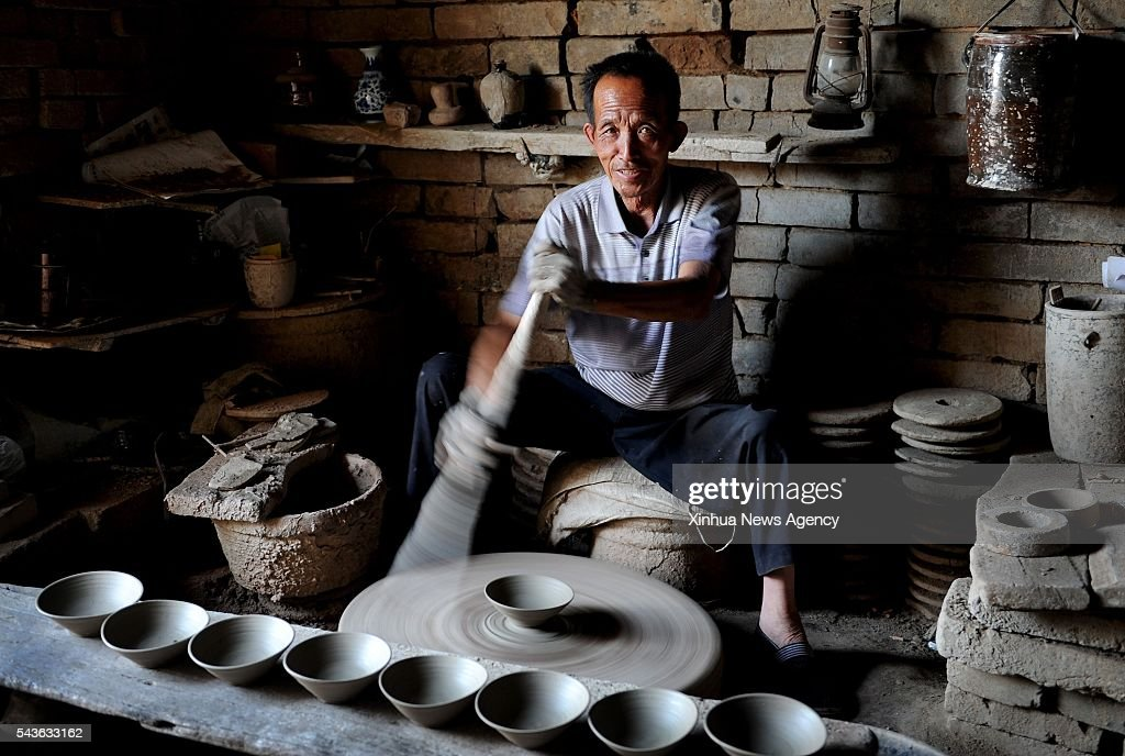 CHENGCHENG, June 29, 2016 -- Folk artist Zhou Tiehuai makes rough porcelain bowls in the Yaotou Kiln tourist zone in Yaotou Township of Chengcheng County, northwest China's Shaanxi Province, June 28, 2016. The site of old folk kilns, covering an area of four square kilometers, has a history of making ceramic products for over a thousand years. The techniques of making ceramics in Yaotou Kiln was listed in the National Intangible Cultural Heritage in 2006.