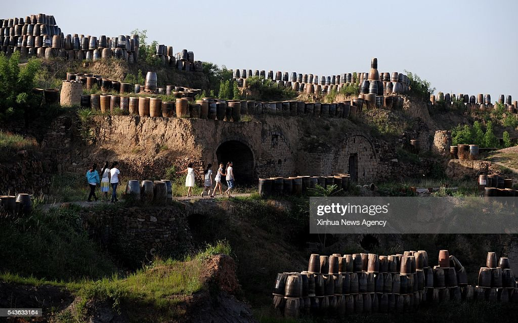 CHENGCHENG, June 29, 2016 -- Students visit the Yaotou Kiln tourist zone in Yaotou Township of Chengcheng County, northwest China's Shaanxi Province, June 29, 2016. The site of old folk kilns, covering an area of four square kilometers, has a history of making ceramic products for over a thousand years. The techniques of making ceramics in Yaotou Kiln was listed in the National Intangible Cultural Heritage in 2006.