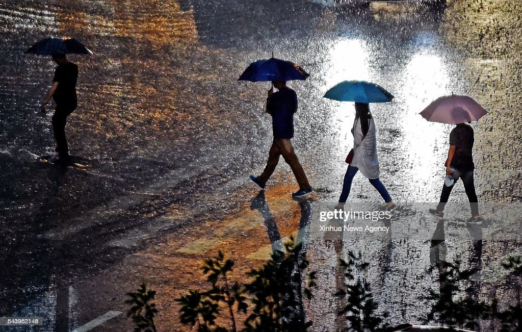SHENYANG, June 30, 2016 -- Pedestrians walk in the rain in the Hunnan District of Shenyang, capital city of northeast China's Liaoning Province, June 30, 2016. The local meteorological authority issued an orange alert for rainstorms Thursday.