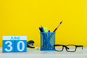 June 30th. Day 30 of month, calendar on yellow background with office suplies. Summer time at work.