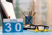 June 30th. Day 30 of month, wooden color calendar on manager workplace background. Summer time. Empty space for text.