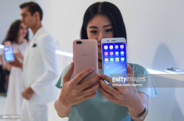 A model presents newlyrelease OPPO smartphone R11 at a press conference in Shenzhen south China's Guangdong Province June 9 2017 The new smartphone...