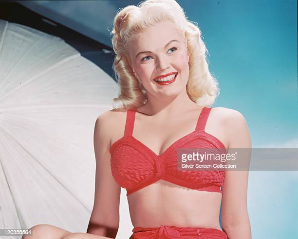 June Haver US actress smiling and wearing a red bra in a studio portrait against a blue background circa 1950
