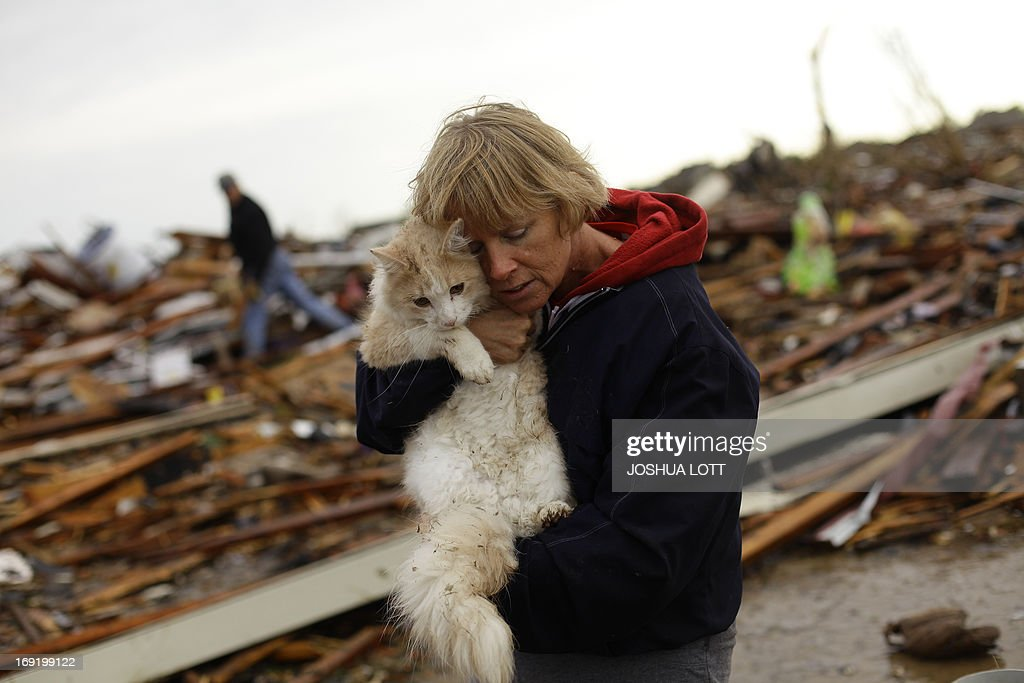 June Simson embraces her cat Sammi after she found him standing on the rubble of her destroyed home on May 21, 2013 in Moore, Oklahoma. Families returned to a blasted moonscape that had been an American suburb Tuesday after a monstrous tornado tore through the outskirts of Oklahoma City, killing at least 24 people. Nine children were among the dead and entire neighborhoods vanished, with often the foundations being the only thing left of what used to be houses and cars tossed like toys and heaped in big piles. AFP PHOTO/Joshua LOTT
