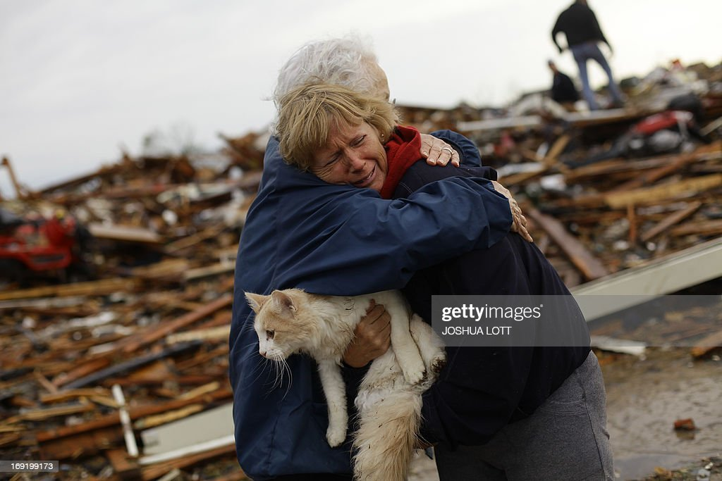 June Simson (R) receives a hug from her neighbor Jo McGee while embracing her cat Sammi after she found him standing on the rubble of her destroyed home on May 21, 2013 in Moore, Oklahoma. Families returned to a blasted moonscape that had been an American suburb Tuesday after a monstrous tornado tore through the outskirts of Oklahoma City, killing at least 24 people. Nine children were among the dead and entire neighborhoods vanished, with often the foundations being the only thing left of what used to be houses and cars tossed like toys and heaped in big piles. AFP PHOTO/Joshua LOTT