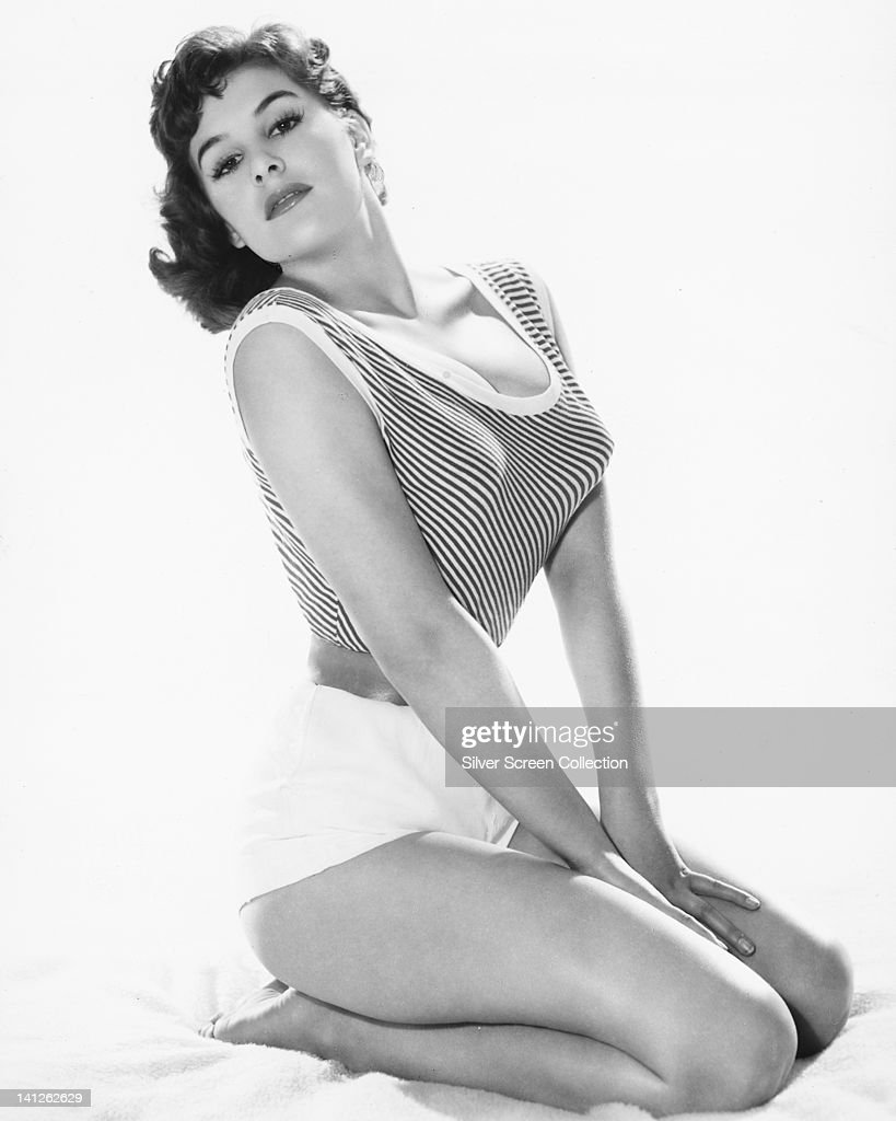 June Wilkinson British actress and pinup model wearing a short sleeveless striped top with a scoop neckline and a pair of white shorts kneeling in a...