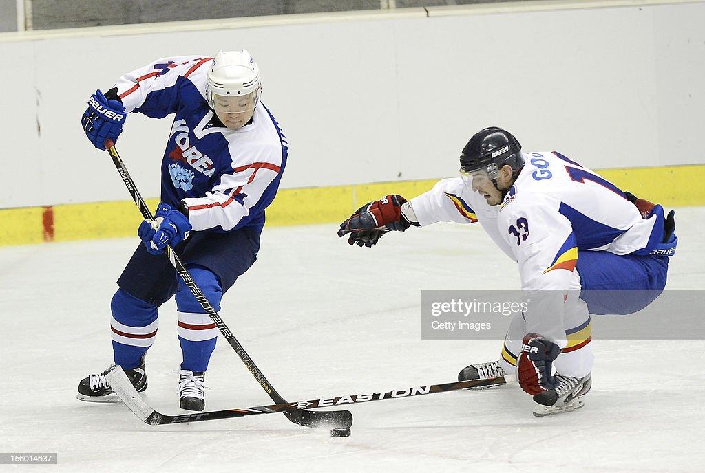 Jung Bungchun #14 of South Korea skates against Attila Goga #13 of Romania during the Ice Hockey Sochi Olympic Pre-Qualification Group J match between South Korea and Romania at Nikko Kirifuri Ice Arena on November 11, 2012 in Nikko, Tochigi, Japan. South Korea won 2-0.