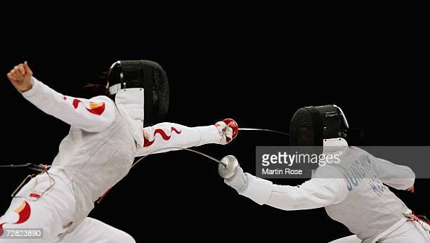 Jung Gil Ok of Republic of Korea competes with Su Wanwen of China in the Women's Team Foil Gold Medal match during the 15th Asian Games Doha 2006 at...