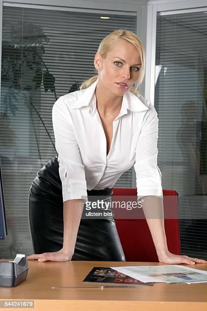 Junge selbstbewusste Frau im Buero mit Lederrock