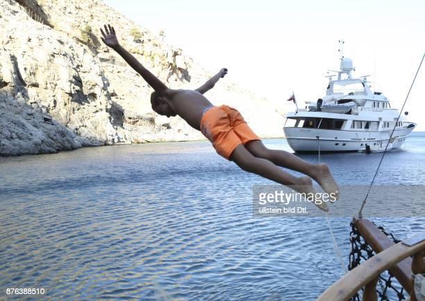 Junge springt von einem Boot ins Meer Im Hintergrund ist eine Yacht zu sehen und ein Gebirge