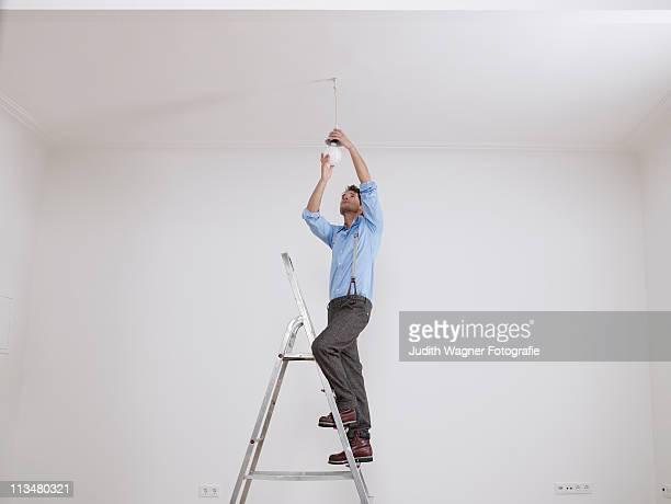 Junger Mannauf Leiter schraubt Glhbirne