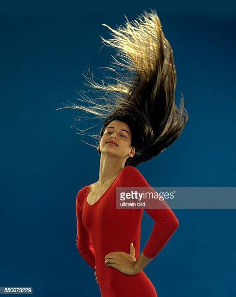 junges Mädchen Gymnastikanzug fliegende lange dunkelblonde Haare undatiert