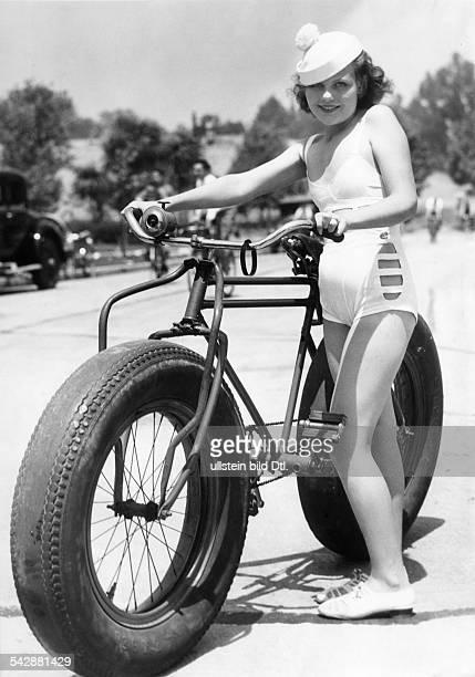 junges Mädchen in einem Bikini mit einemFahrrad das übergrosse Reifen hatHollywood 1934