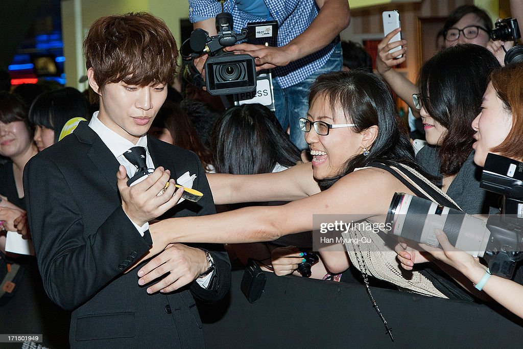 Junho of South Korean boy band 2PM poses with fans the 'Cold Eyes' VIP screening at Coex Mega Box on June 25, 2013 in Seoul, South Korea. The film will open on July 03 in South Korea.