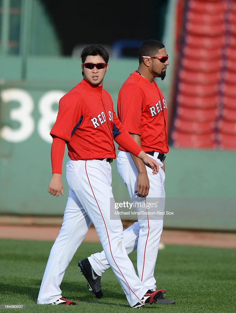 Junichi Tazawa #36 and Franklin Morales #56 of the Boston Red Sox walk through the outfield during a tema workout a day before the start of the American League Championship Series against the Detroit Tigers on October 11, 2013 at Fenway Park in Boston, Masschusetts.