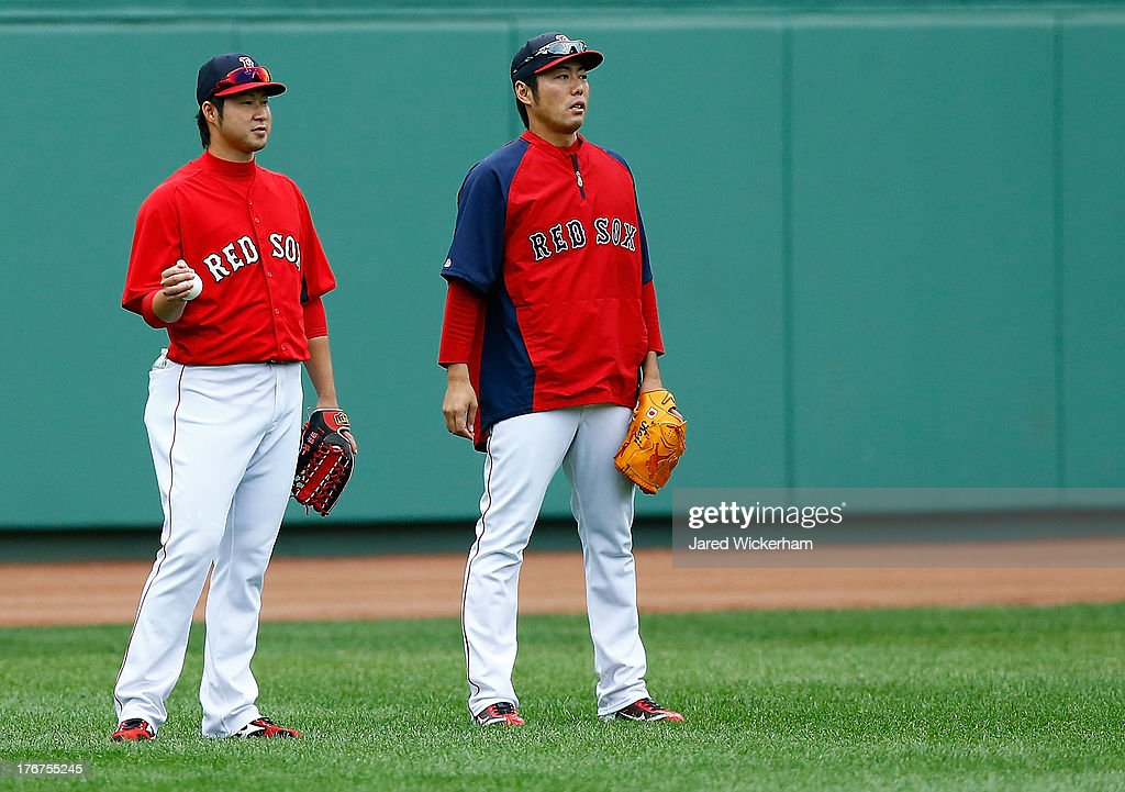 Junichi Tazawa #36 and Koji Uehara #19 of the Boston Red Sox warm up during batting practice prior to the game against the New York Yankees on August 18, 2013 at Fenway Park in Boston, Massachusetts.