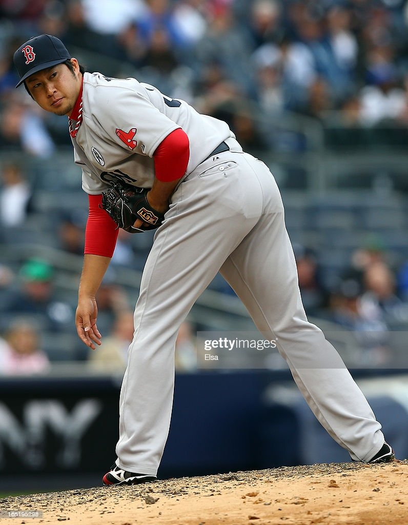 Junichi Tazawa #36 of the Boston Red Sox checks the runner in the eighth inning against the New York Yankees during Opening Day on April 1, 2013 at Yankee Stadium in the Bronx borough of New York City.