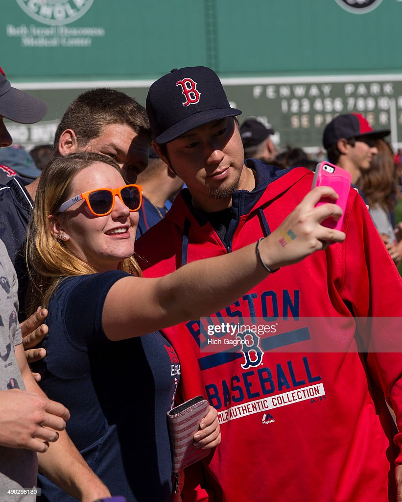 Junichi Tazawa #36 of the Boston Red Sox poses for a photo with a fan during 'Photo on the Field Day'at Fenway Park before a game against the Baltimore Orioles on September 27, 2015 in Boston, Massachusetts.