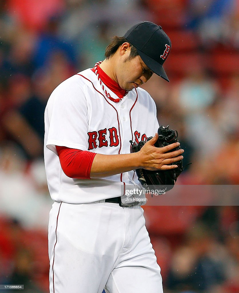 Junichi Tazawa #36 of the Boston Red Sox reacts after giving up a home run in the 8th inning against the Colorado Rockies at Fenway Park on June 26, 2013 in Boston, Massachusetts.