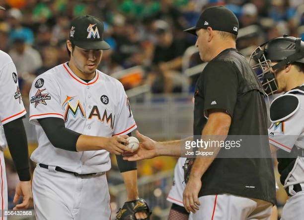 Junichi Tazawa of the Miami Marlins gives the ball to pitching coach Juan Nieves in the seventh inning of play against the Atlanta Braves at Marlins...