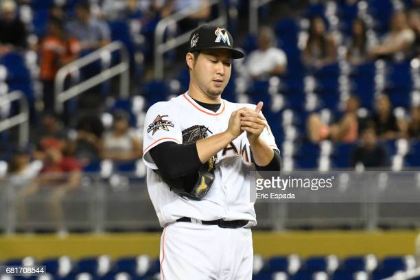 Junichi Tazawa of the Miami Marlins rubs the baseball between pitches during the seventh inning against the St Louis Cardinals at Marlins Park on May...