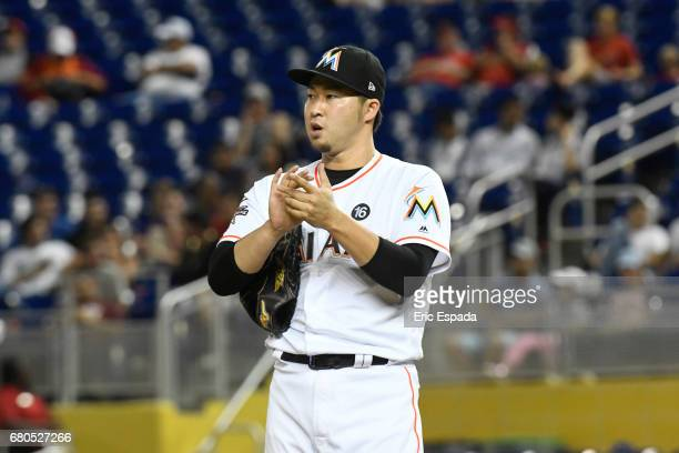 Junichi Tazawa of the Miami Marlins rubs the baseball in between pitches during the eighth inning against the St Louis Cardinals at Marlins Park on...