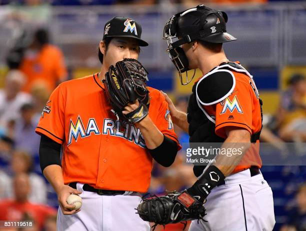 Junichi Tazawa of the Miami Marlins speaks with catcher JT Realmuto in the eighth inning during the game between the Miami Marlins and the Colorado...