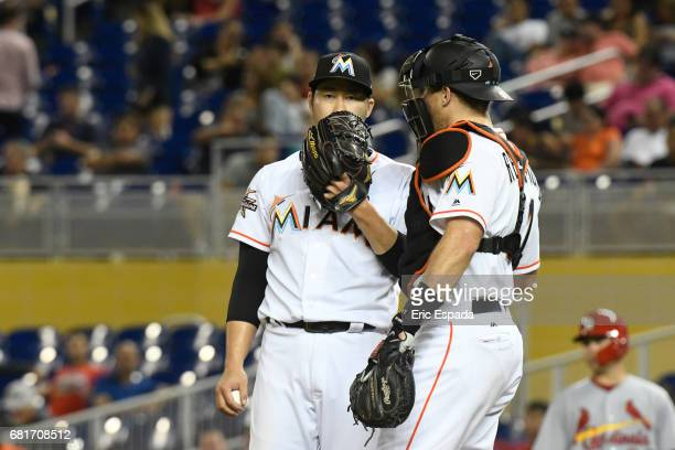 Junichi Tazawa of the Miami Marlins talks with JT Realmuto inbetween pitches during the seventh inning against the St Louis Cardinals at Marlins Park...