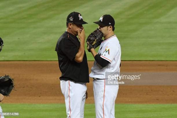 Junichi Tazawa of the Miami Marlins talks with Pitching Coach Juan Nieves during the sixth inning against the Houston Astros at Marlins Park on May...