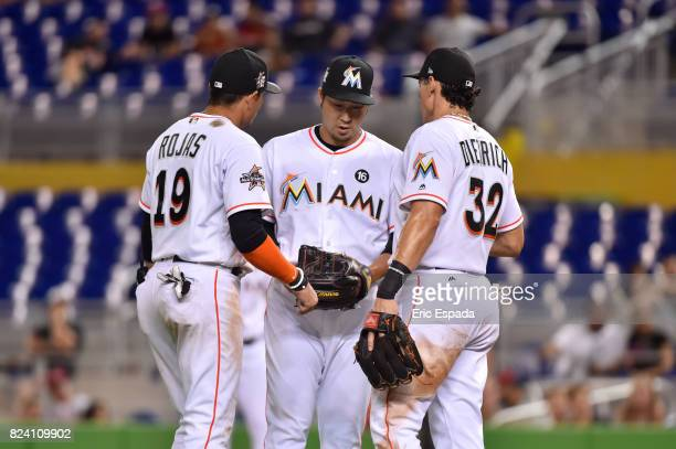 Junichi Tazawa of the Miami Marlins talks with teammates Miguel Rojas and Derek Dietrich inbetween batters during the game against the Cincinnati...