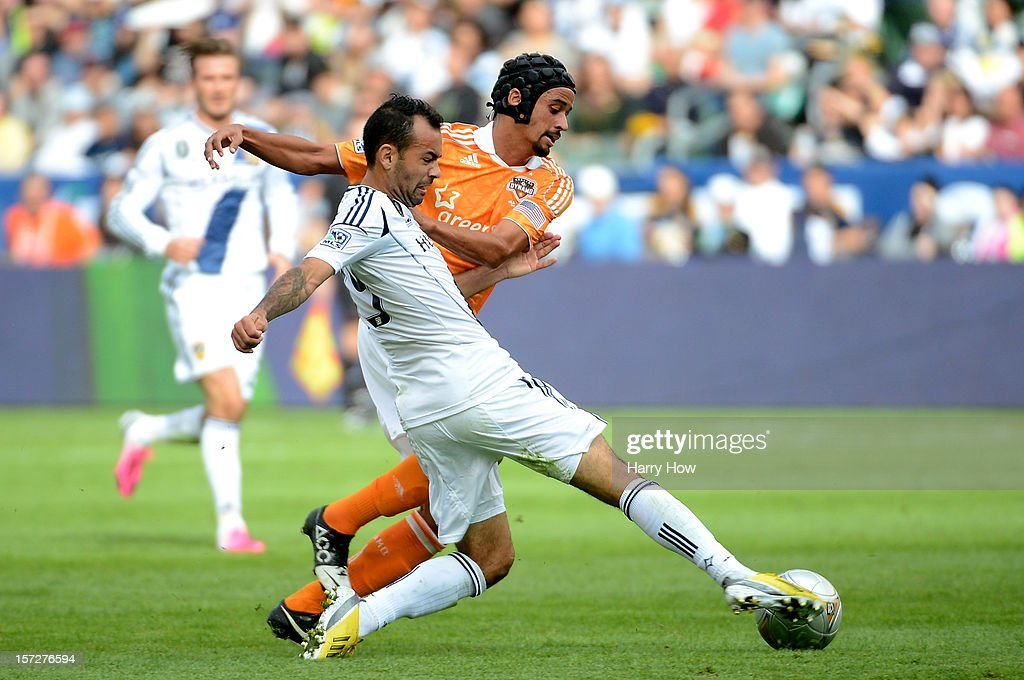 Juninho of Los Angeles Galaxy and Calen Carr of Houston Dynamo battle for the ball in the first half in the 2012 MLS Cup at The Home Depot Center on...