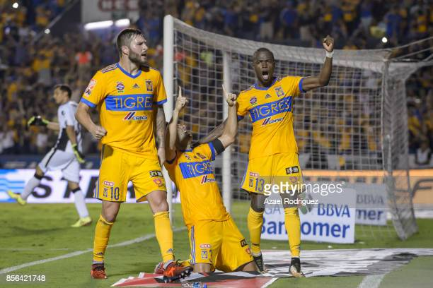 Juninho of Tigres celebrates with teammates Andre Gignac and Enner Valencia after scoring his team's winning goal via penalty during the 12th round...